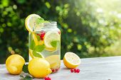 Homemade Lemonade With Fresh Lemons, Mint And Cranberries. A Can Of Lemonade Against A Background Of poster