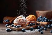 Muffins And Blueberries Sprinkled With Powdered Sugar On An Old Wooden Table. poster