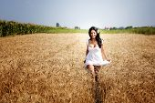 Happy free young woman running in grain field