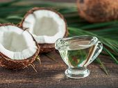 Liquid Coconut Mct Oil And Halved Coco-nut On Wooden Table. Health Benefits Of Mct Oil. Mct Or Mediu poster