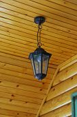 picture of flambeau  - Old metal chandelier on a wooden ceiling - JPG