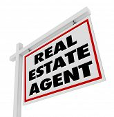 The words Real Estate Agent on a home or house for sale sign advertising an agency and its professio
