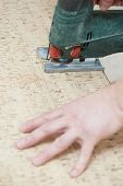 Close-up process of cutting cork floor board with jigsaw