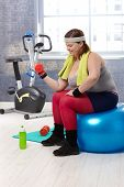 Plump woman exercising with dumbbells at the gym.