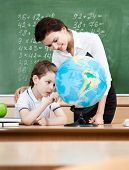 Little schoolboy studies geography with terrestrial globe