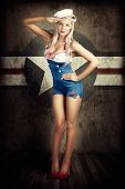 stock photo of army  - Grunge Portrait Of A Beautiful American Retro Female Cadet Dressed In Navy Uniform While Saluting In A Military Pin Up Girl Concept On Army Star Background - JPG