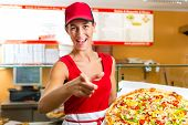 image of take out pizza  - Woman holding a whole pizza in hand and asking you to ordering a pizza - JPG