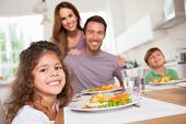 Family smiling at the camera at dinner table in kitchen