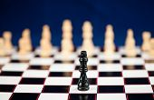 One black chessman standing at the chessboard white ones standing behind