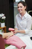 Portrait of young woman buffering toe nails at spa center