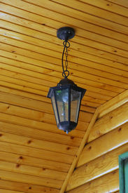 stock photo of flambeau  - Old metal chandelier on a wooden ceiling - JPG