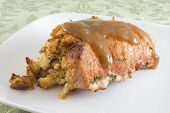 stock photo of pork chop  - Stuffed pork chop covered in gravy on plate