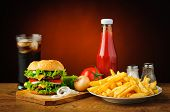 stock photo of hamburger  - still life with hamburger menu french fries cola drink tomato ketchup salt and pepper - JPG