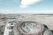 Barbed Wire Roll On A Rock With Wind Turbines