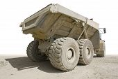 picture of dumper  - back side of a dirty dumper in sunny ambiance partly isolated in white back - JPG