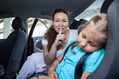 Mother With Shh Gesture When Daughter Asleep In Car Safety Seat