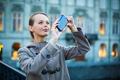 Elegant, young woman taking a photo with her cell phone camera while traveling (shallow DOF; color t