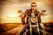stock photo of driving  - Biker man wearing a leather jacket and sunglasses sitting on his motorcycle looking at the sunset - JPG