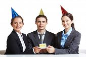 Portrait of young business partners in birthday caps holding piece of cake on saucer and looking at
