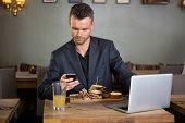 Young businessman text messaging on cellphone while having sandwich in coffeeshop