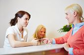 Woman giving her smartcard to receptionist at dentist office