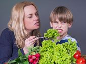 Little boy  refusing to eat green salad