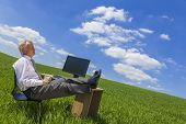 Man or male businessman relaxing feet up at a desk with a computer in a green field drinking tea or coffee