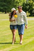 stock photo of barefoot  - Happy young couple walking in park barefoot - JPG