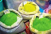 Green henna powder in bags on souk market in Muscat