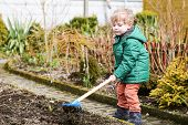 stock photo of hoe  - Little boy in spring with garden hoe planting and gardening outdoors - JPG