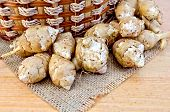 stock photo of jerusalem artichokes  - Jerusalem artichoke tubers wicker basket on burlap background napkin of burlap and wooden boards - JPG