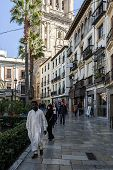Black Man In White Robes Walking Down The Street, Granada, Andalusia, Spain