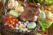 foto of easter candy  - Chocolate Easter Bunny in a Basket with Assorted Candy - JPG