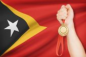 Medal In Hand With Flag On Background - Democratic Republic Of Timor-leste