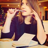 young woman with notebook in modern cafe
