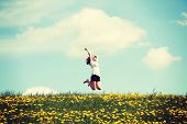 foto of meadows  - Happy woman jumping on blossom meadow - JPG
