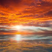 Reflection of Beautiful Sunset / Orange and Red Majestic Clouds above Water