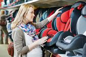 woman choosing child car seat for newborn baby in shop supermarket