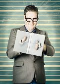 image of bookworm  - Funny portrait of a male nerd holding book with fingers poking through plot hole twist - JPG