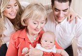 Happy family portrait, cheerful mother and father standing near granny holding newborn baby on hands