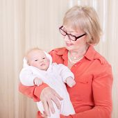 Happy granny holding newborn kid at home, enjoying sweet little grandchild, hugging with love, family happiness concept