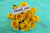 Thank you note and yellow roses on green background