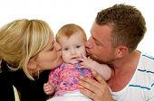 Mother and father are kissing their sweet baby 4 month old baby.