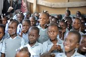 KOLMINY, HAITI - FEBRUARY 12, 2014: Editorial image of unidentified children in a crowded classroom in Kolminy, Haiti on February 12, 2014.  Shallow depth of field with focus on center girl.