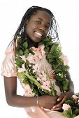 A beautiful tween girl dressed up in peach and adorned with leis of leaves and flowers.  On a white background.