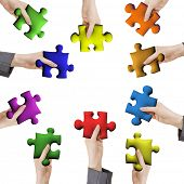 Concept of help or working together, hands holding various color puzzle pieces on white background.