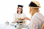 Teen girls having a tea party together.  White background.
