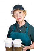 Senior woman serving coffee because she can't afford retirement. Isolated on white.