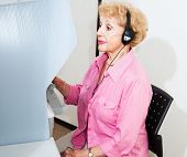 Hearing disabled senior woman voting on touch screen machine with headphones.
