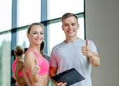 fitness, sport, exercising and diet concept - smiling young woman with personal trainer in gym showi
